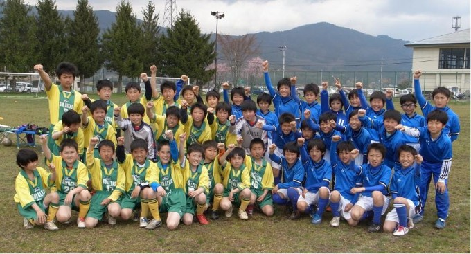 試合後、記念写真に納まるFCサンアルタス大船渡(黄)とヴァレンテとおの(青)