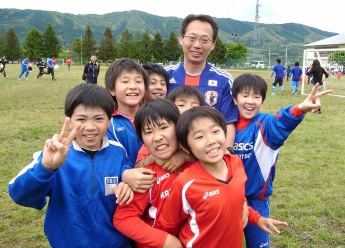 被災地の子供たちと笑顔で写真におさまる岡田武史氏