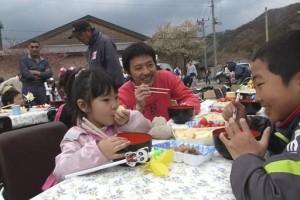 おいしそうにボランティアの用意した食べ物を頬張る家族