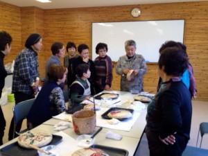 柿渋塗りの方法を説明する佐藤美喜子さん(写真奥)